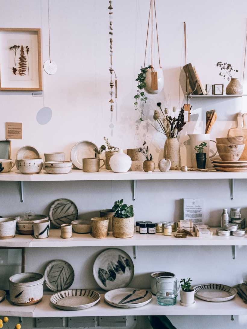 assorted ceramics on wooden shelves