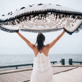 Women in white dress holds up beach towel near beach as it waves in the wind.