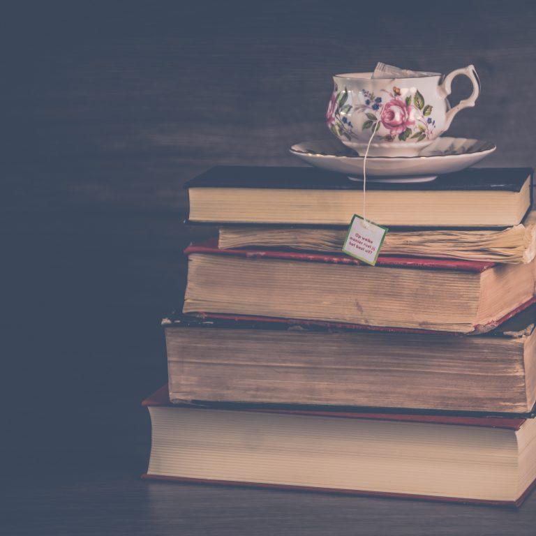 pile of hardbound books with floral ceramic mug