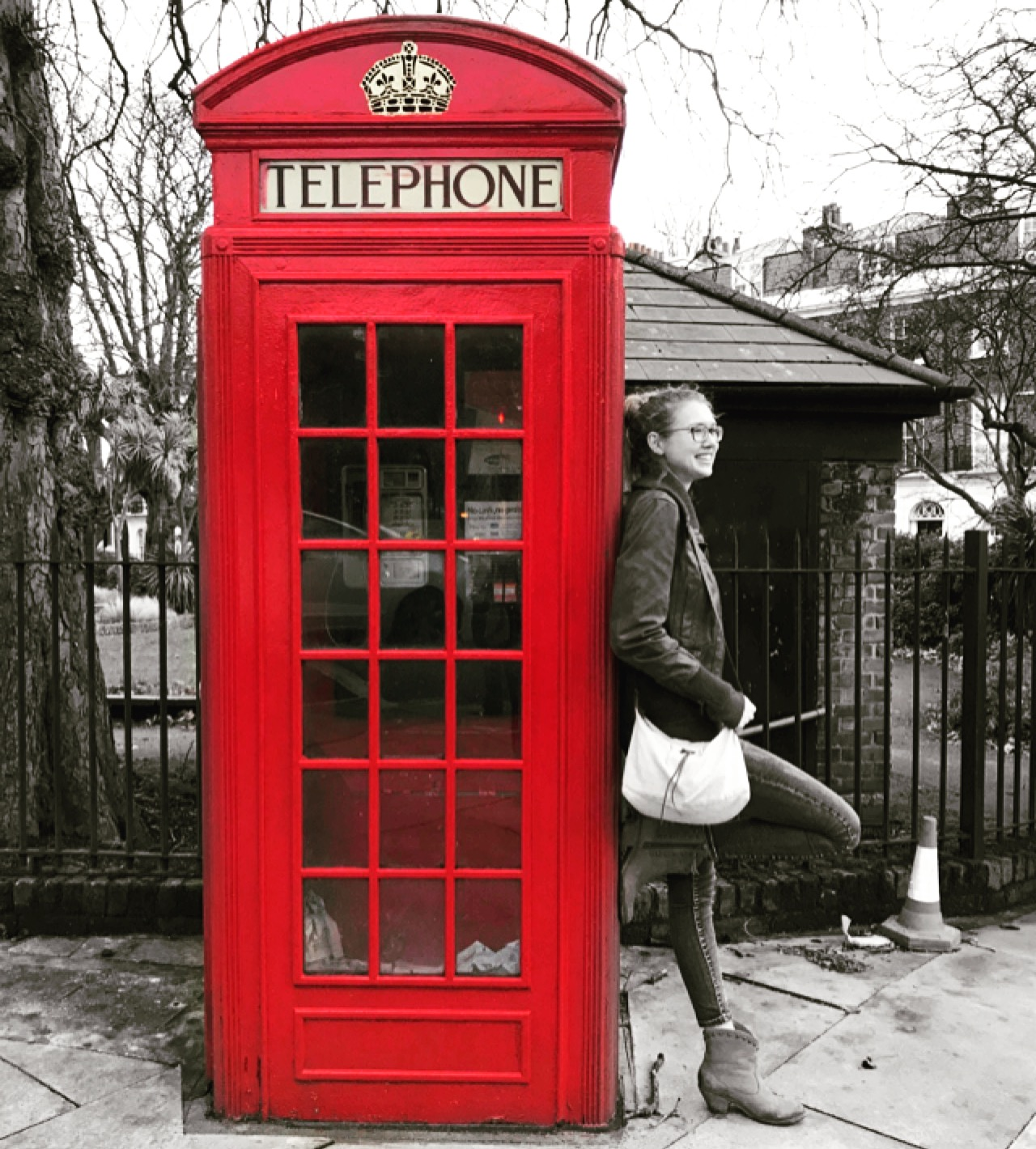 women leans against red telephone booth
