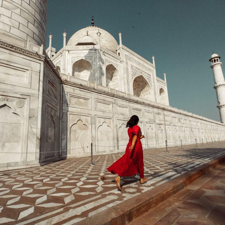 woman in red dress passes through taj mahal