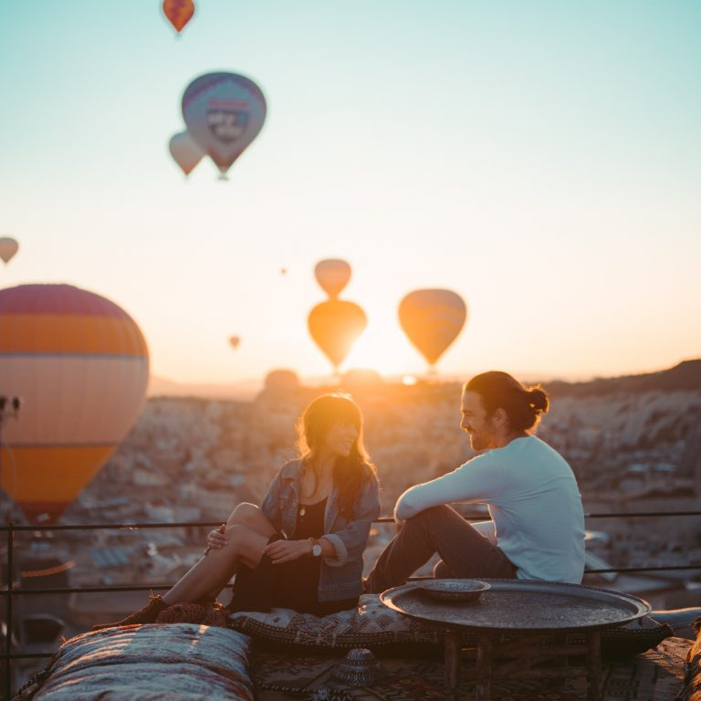 couple sitting on rooftop during sunset in tukey