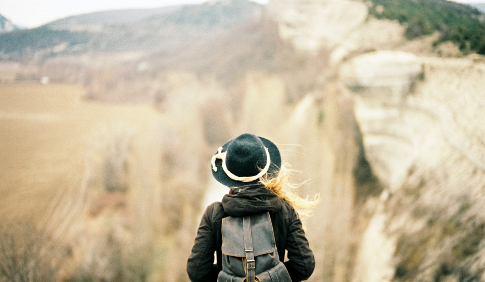 women in hat and backpack staring out at scenery