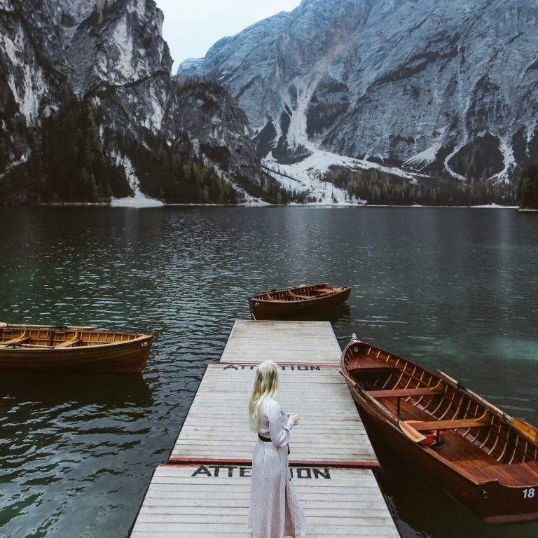 women in white dress on a dock staring at mountains