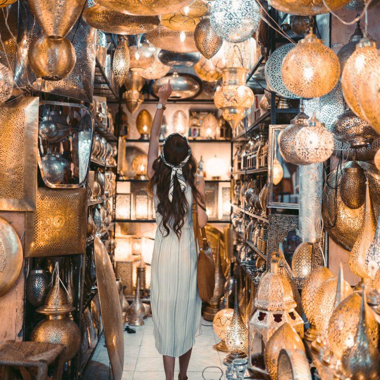 women in white dress walks inside light store
