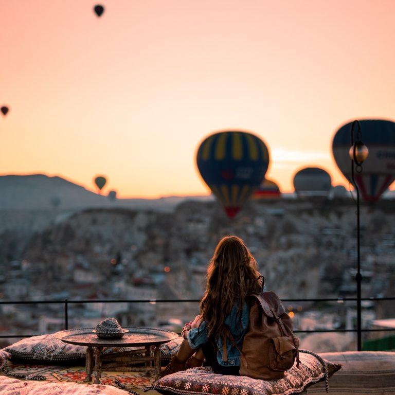 woman looking out at hot air balloons