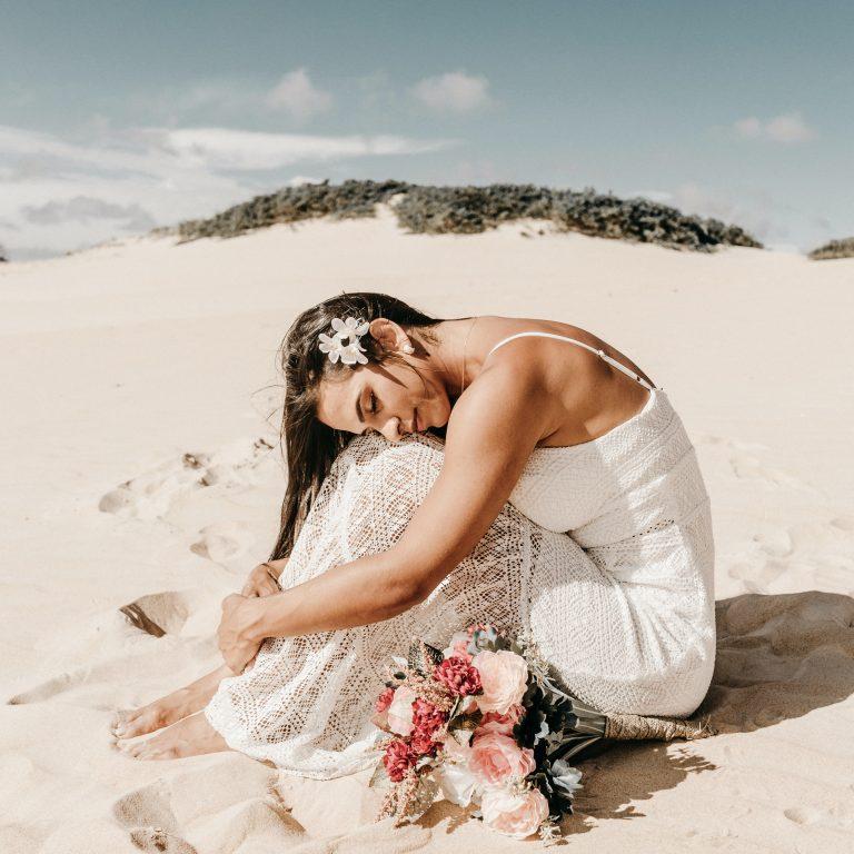 women sitting on sand in wedding dress