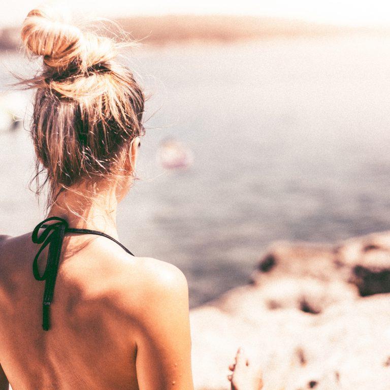 woman in swimsuit standing near ocean